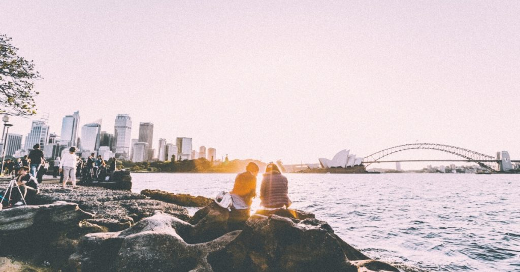Two people sitting and standing at shore watching the sunset near the Sydney Opera House in panorama photography