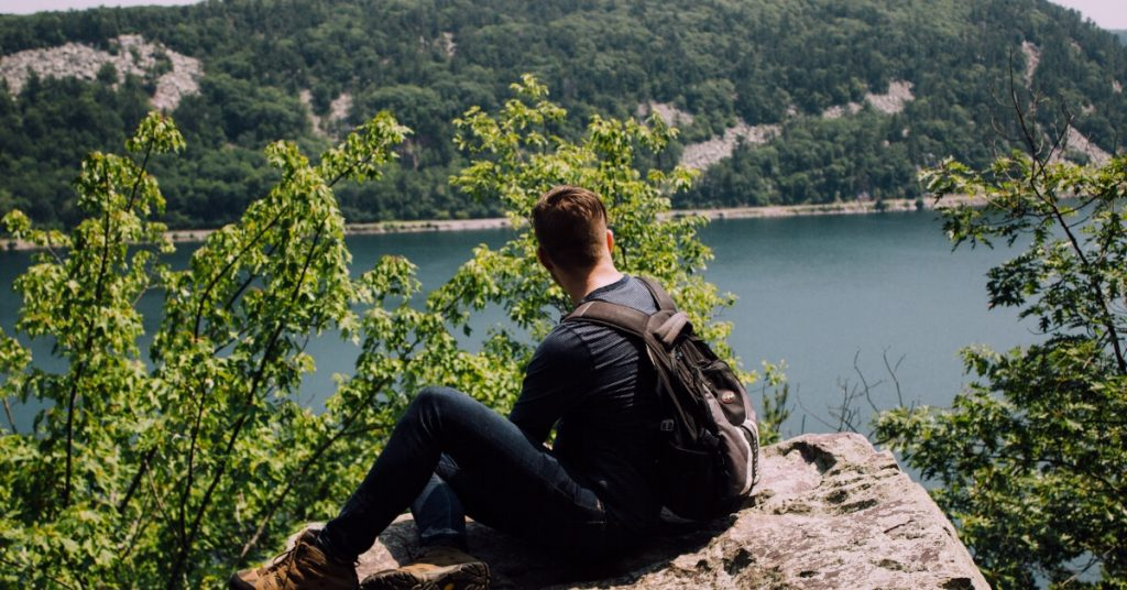 man sitting on a high rock overlooking a body of water