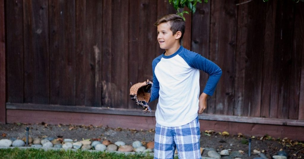 a boy playing softball in the backyard