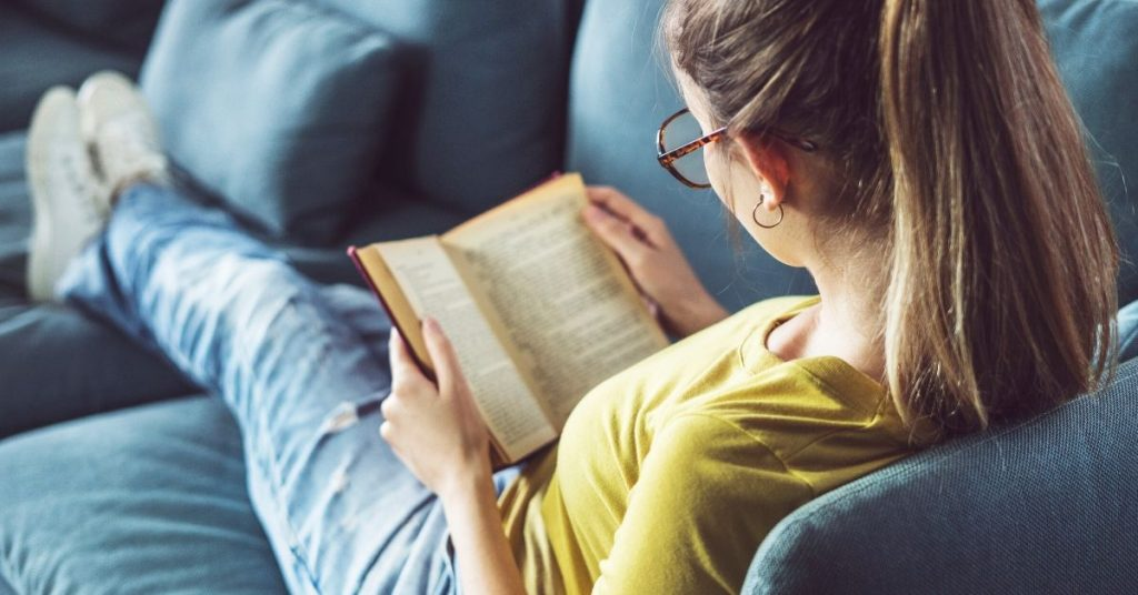 photo of a girl reading on the couch at home