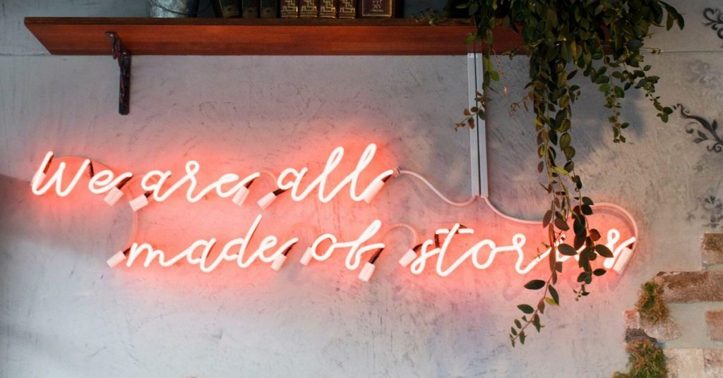 a neon sign on a wall which says we're all made of stories