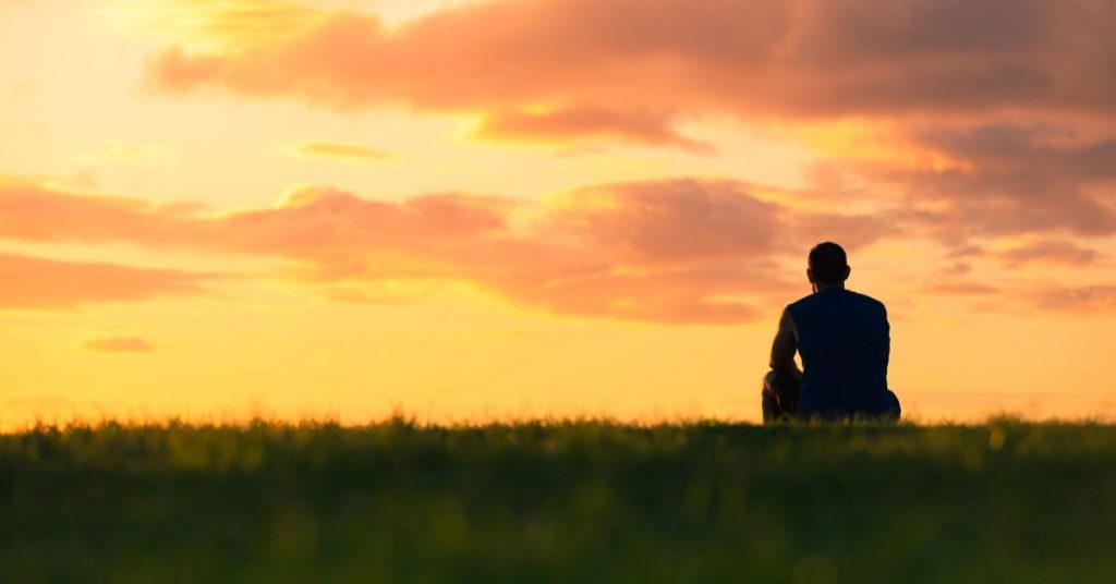 photo of a silhouette of a man sitting on a hill at sunset