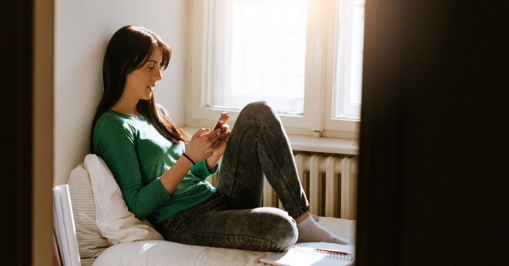 photo of a teenage girl sitting on her bed holding a phone while on social media