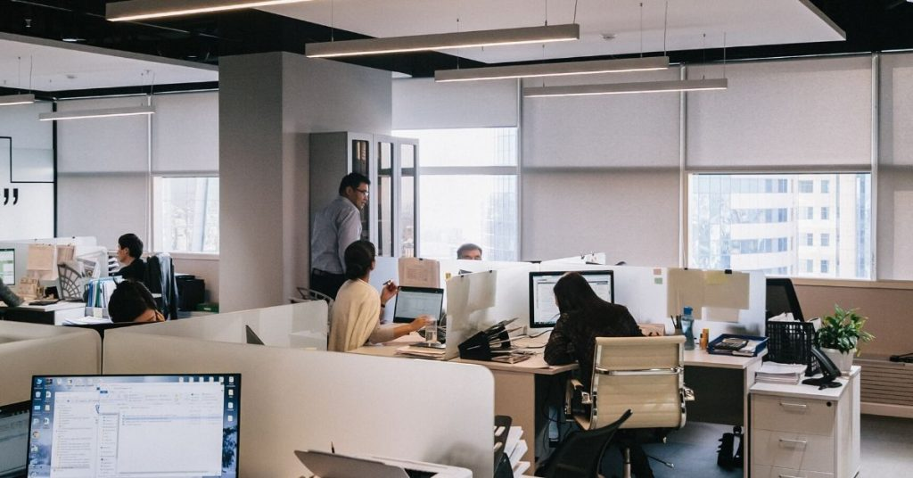 photo shows desks and people inside an office building