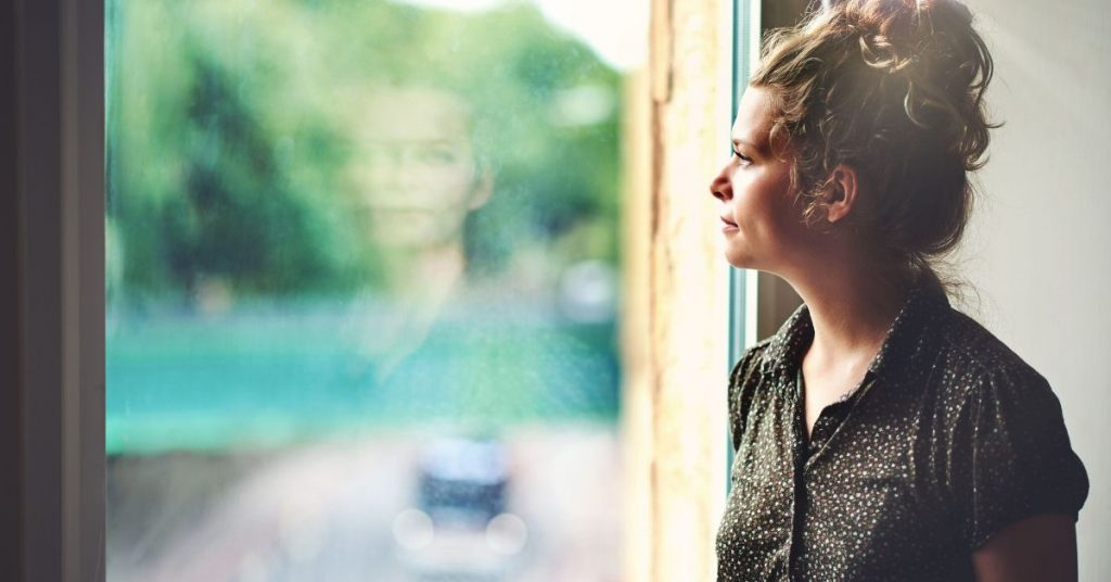 photo of a woman looking out the window