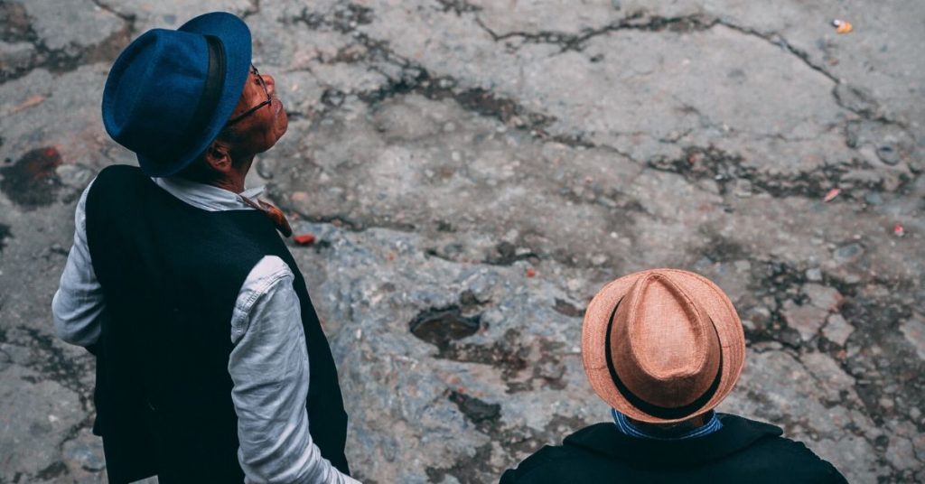 photo shows two men of colour wearing wide brimmed hats looking up