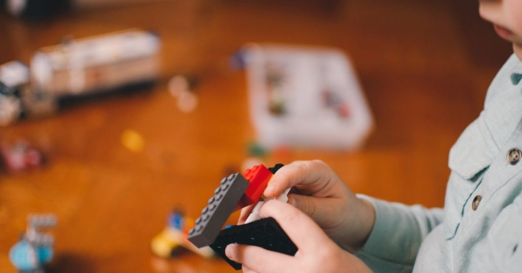 young boy playing with lego