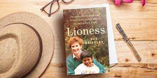 copy of Lioness book on table with hat glasses and pen